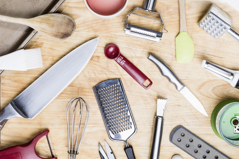 Assorted kitchen utensils on a wooden table.